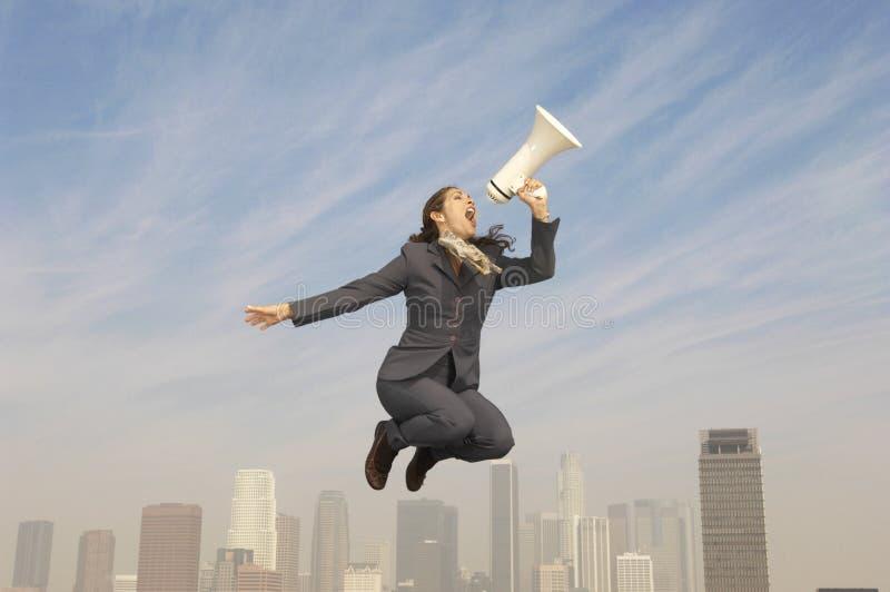 Affärskvinna Shouting Into Megaphone ovanför stad arkivbild