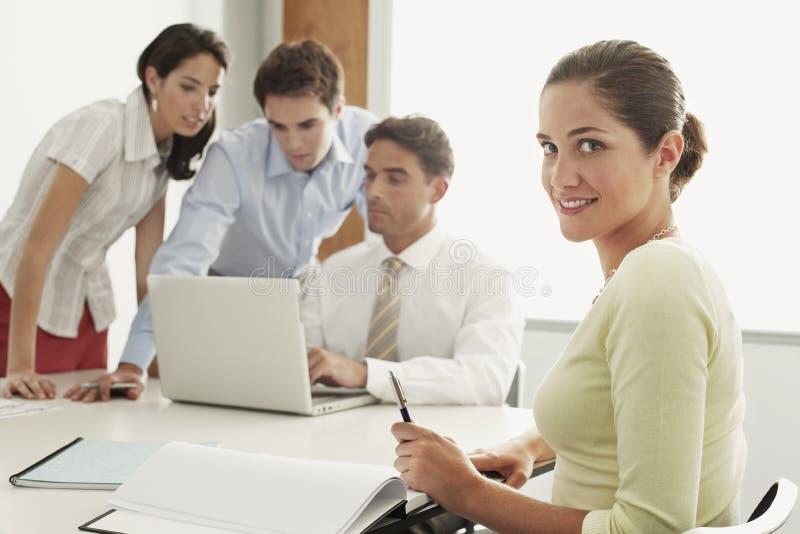 Affärskvinna Sitting With Colleagues som arbetar på bärbara datorn på skrivbordet fotografering för bildbyråer