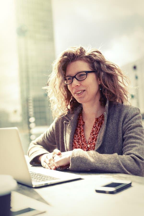 Affärskvinna Sitting Outdoors som arbetar på hennes dator royaltyfri fotografi