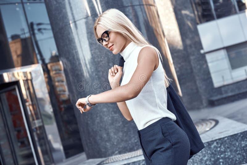 Affärskvinna som är blond i exponeringsglas som skynda sig till ett möte Hon ler royaltyfri foto