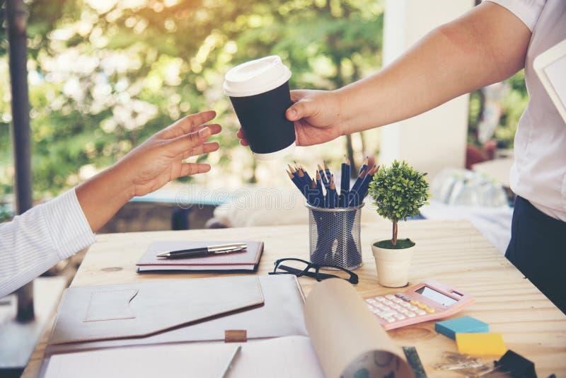 Affärskvinna som är mötet för arbete för medarbetarepartnerlaget som ger en kopp kaffe arkivbilder
