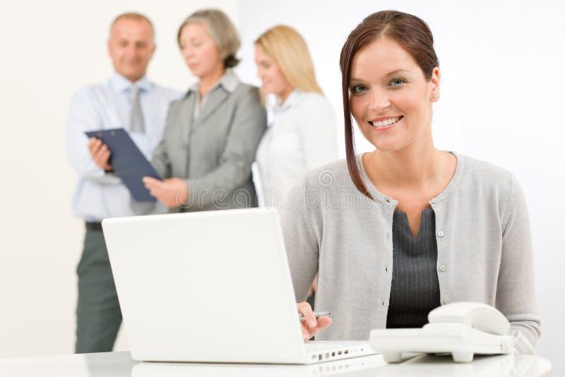 Affärskvinna som är nätt med kollegor som diskuterar royaltyfria bilder