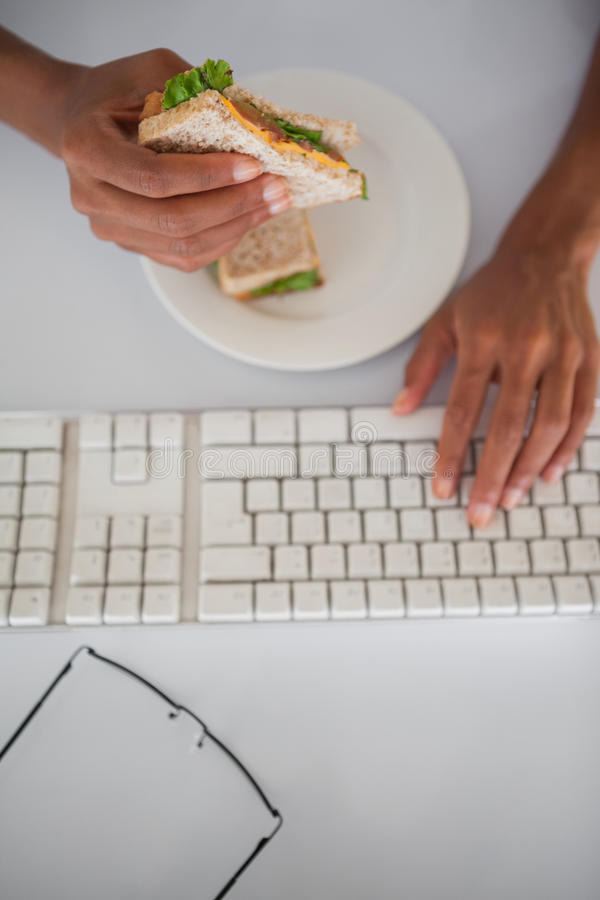 Affärskvinna som äter en smörgås på hennes skrivbord arkivfoto