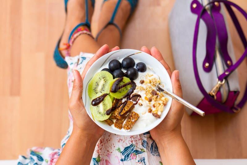 Affärskvinna som äter rå strikt vegetariantuggor för mellanmål royaltyfri foto