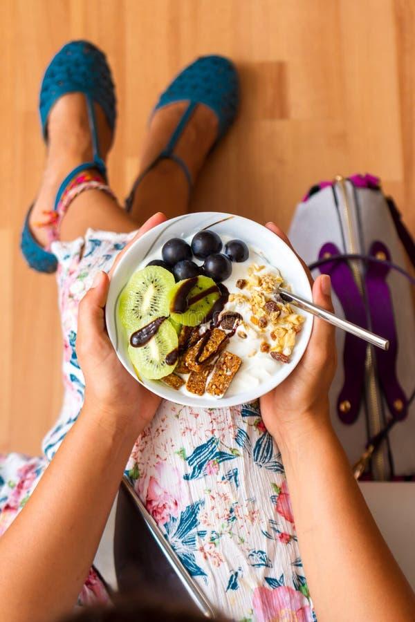 Affärskvinna som äter rå strikt vegetariantuggor för mellanmål arkivbild