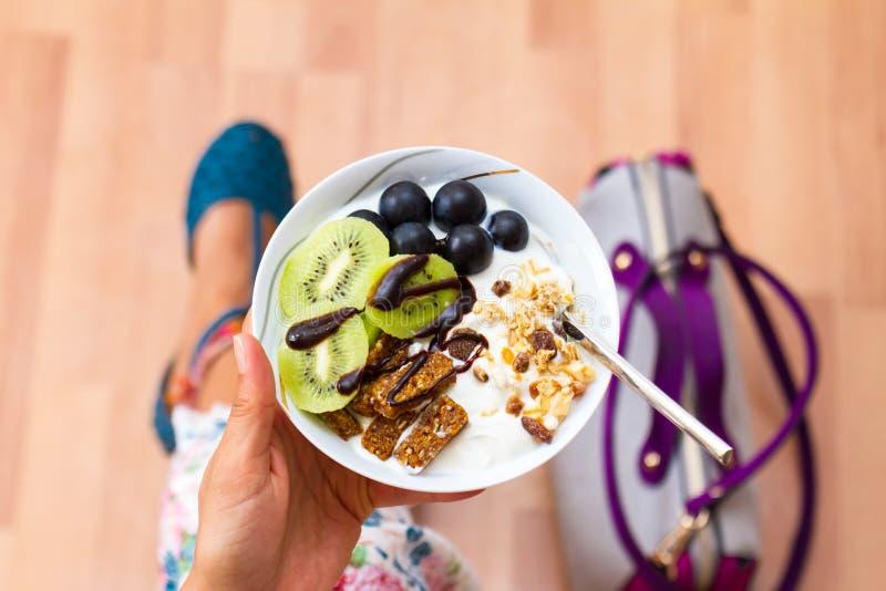 Affärskvinna som äter rå strikt vegetariantuggor för mellanmål royaltyfri bild