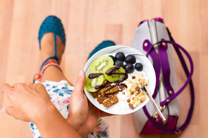 Affärskvinna som äter rå strikt vegetariantuggor för mellanmål arkivbilder