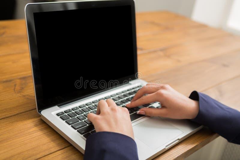 Affärskvinna som använder bärbara datorn på arbetsplatsen, närbild royaltyfri bild
