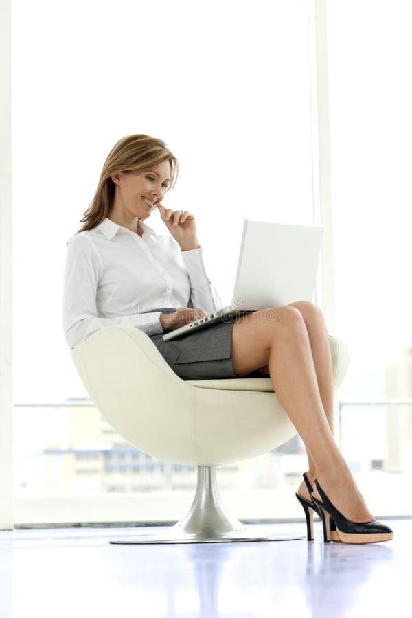 Affärskvinna som använder bärbara datorn på knä royaltyfri foto
