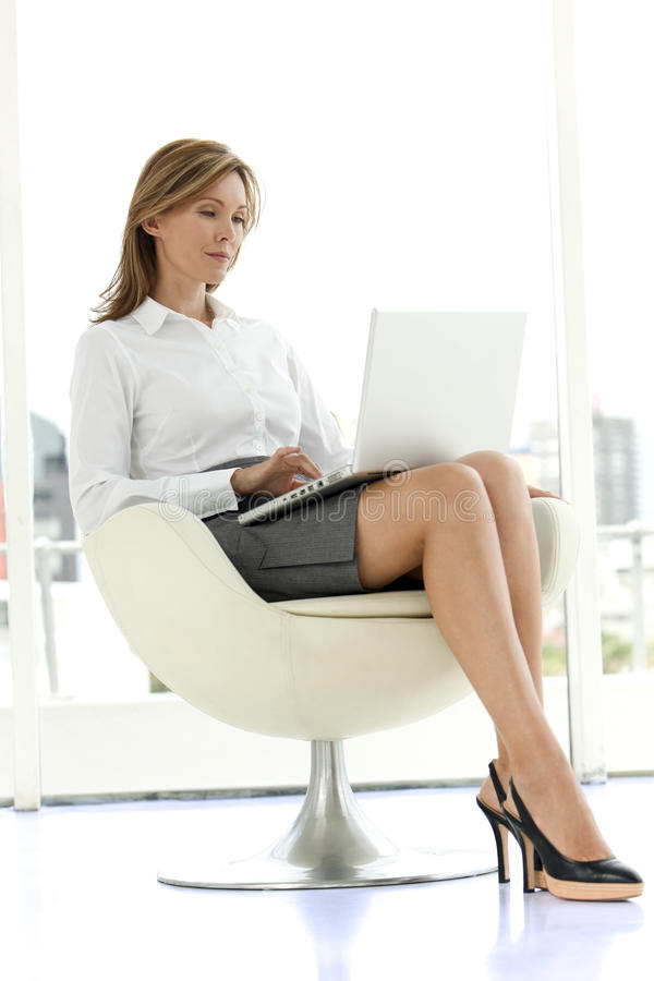 Affärskvinna som använder bärbara datorn på knä royaltyfri bild