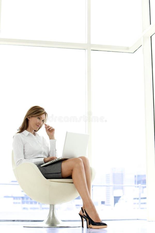 Affärskvinna som använder bärbara datorn på knä arkivfoto