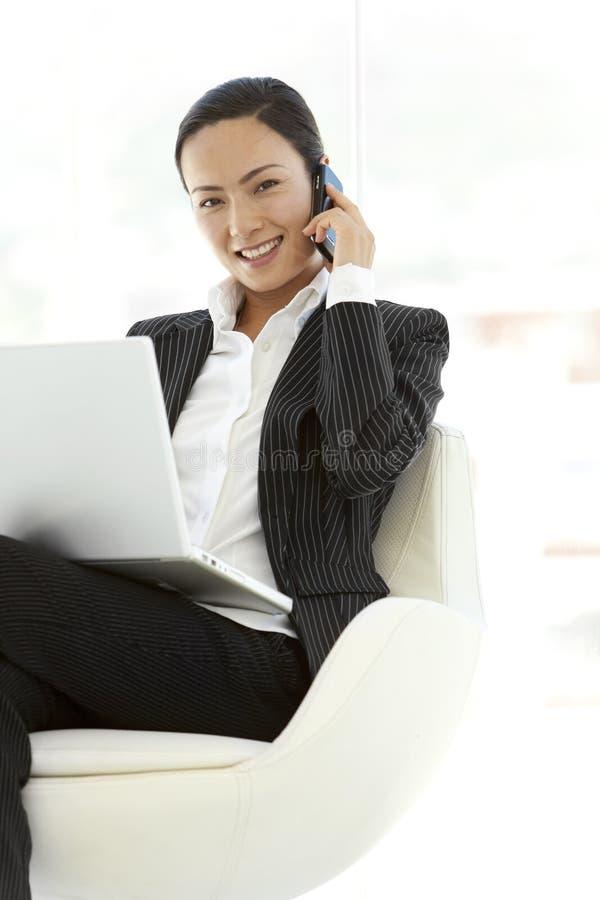 Affärskvinna som använder bärbara datorn på knä arkivbild
