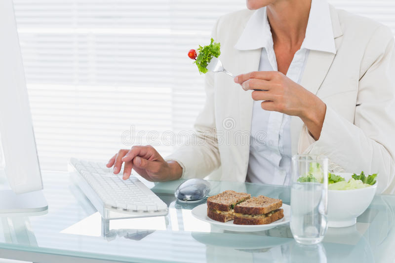 Affärskvinna som använder datoren, medan äta sallad på skrivbordet arkivfoto