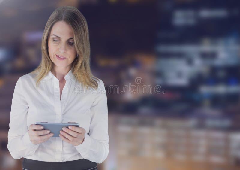 Affärskvinna som använder en digital minnestavla mot byggnader i bakgrund arkivbilder
