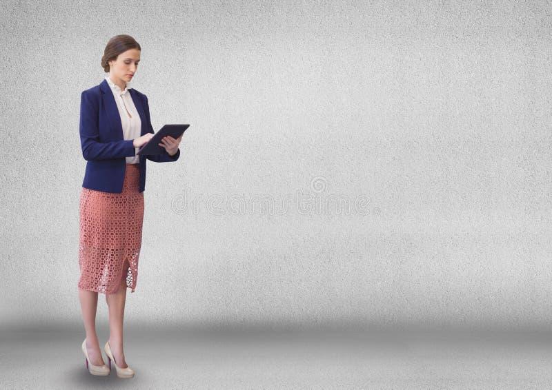 Affärskvinna som använder en minnestavla mot grå väggbakgrund royaltyfri fotografi