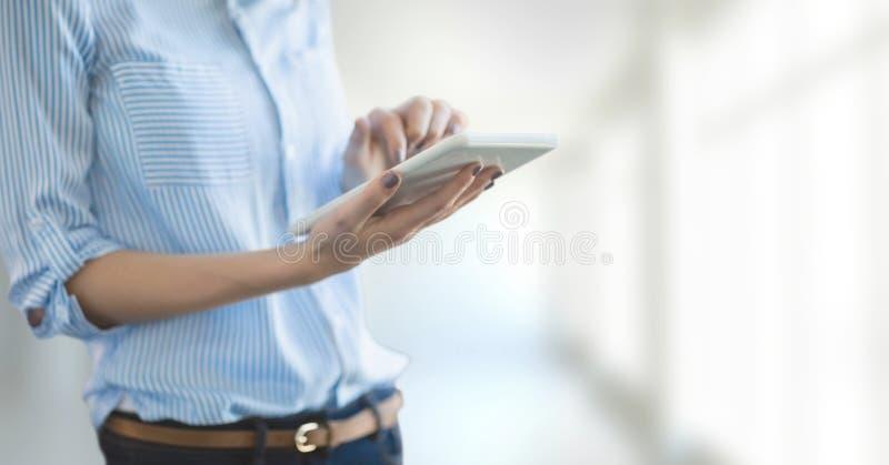 Affärskvinna som använder en minnestavla mot vit suddig bakgrund royaltyfri fotografi