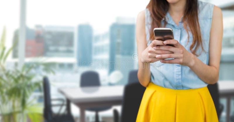 Affärskvinna som använder en telefon mot kontorsbakgrund royaltyfri foto