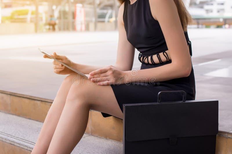 Affärskvinna som använder en utomhus- minnestavladator och arbete arkivfoton