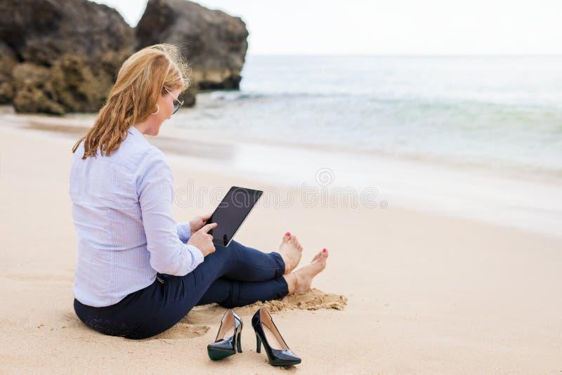 Affärskvinna som använder minnestavladatoren, medan sitta på stranden royaltyfri fotografi