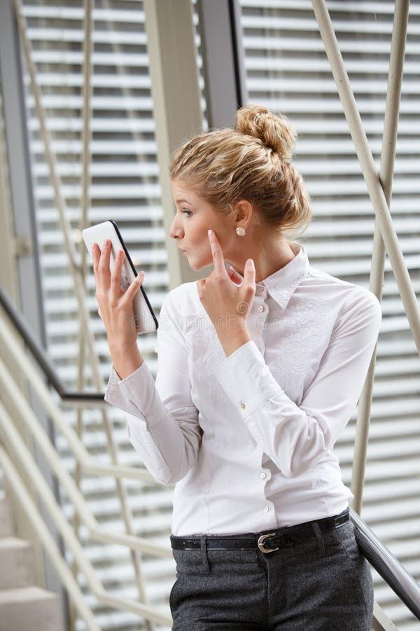 Affärskvinna som använder minnestavlan som en spegel royaltyfria foton