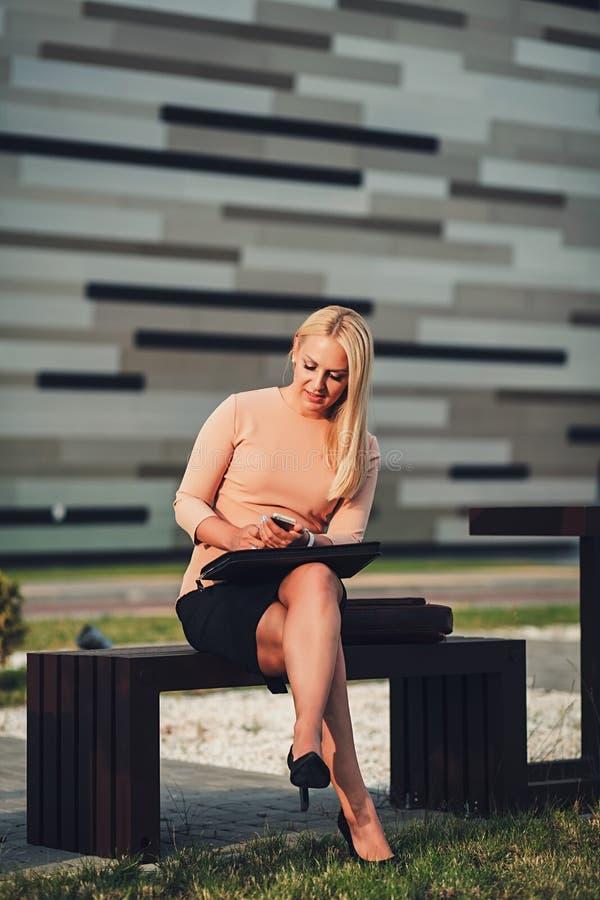 Affärskvinna som använder mobil applikation på mobiltelefonen arkivfoton