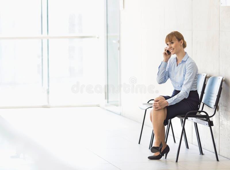 Affärskvinna som använder mobiltelefonen, medan sitta på stol i regeringsställning royaltyfria bilder