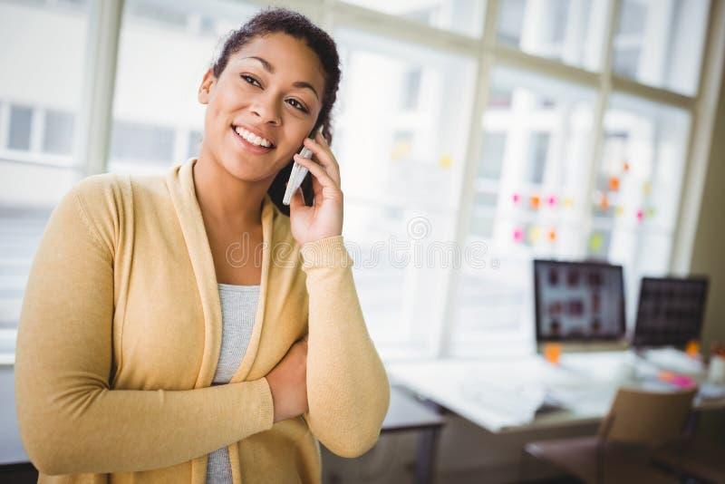 Affärskvinna som använder mobiltelefonen på det idérika kontoret royaltyfri fotografi