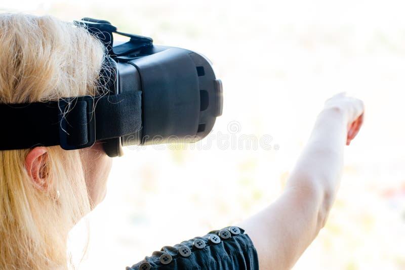 Affärskvinna som använder virtuell verklighetexponeringsglas i en stads- miljö Ny teknik i affär & x28; eller arkitektur royaltyfri fotografi
