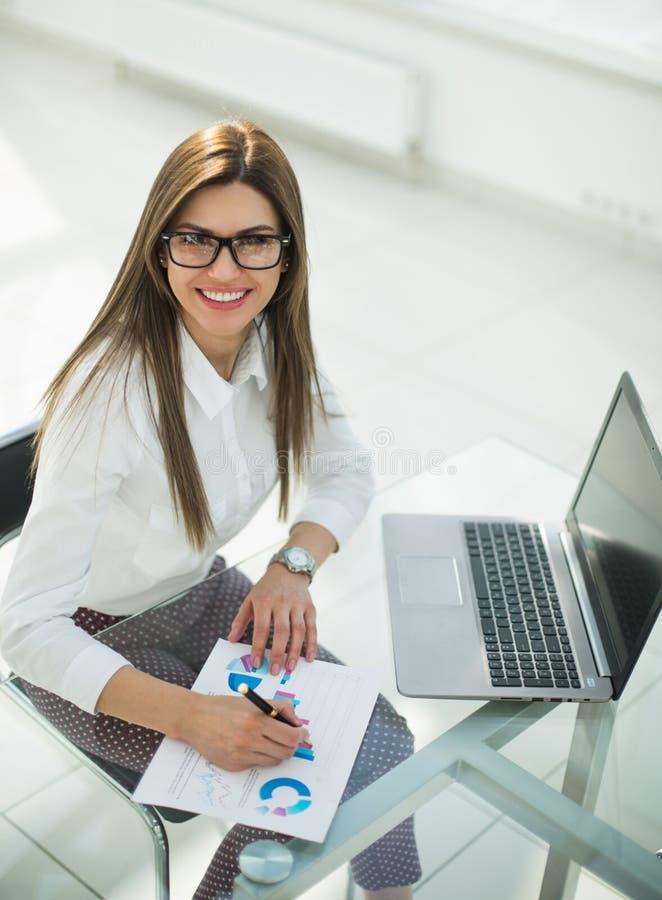 Affärskvinna som arbetar, genom att kontrollera den finansiella rapporten royaltyfri foto