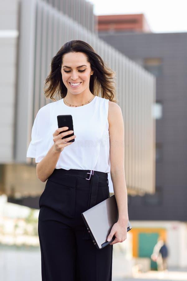 Affärskvinna som arbetar med hennes smarta telefon- och bärbar datordet fria arkivfoton