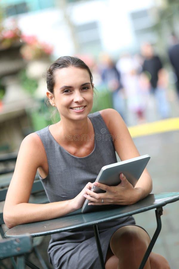 Affärskvinna som arbetar med minnestavlan i staden royaltyfri foto