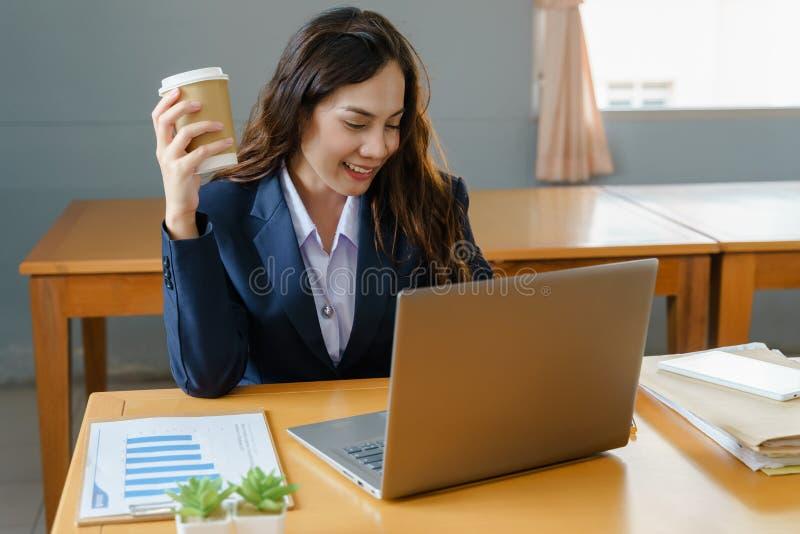 Affärskvinna som arbetar och dricker kaffe, i att koppla av sätt royaltyfri bild