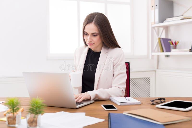 Affärskvinna som arbetar på bärbara datorn på kontoret royaltyfri bild