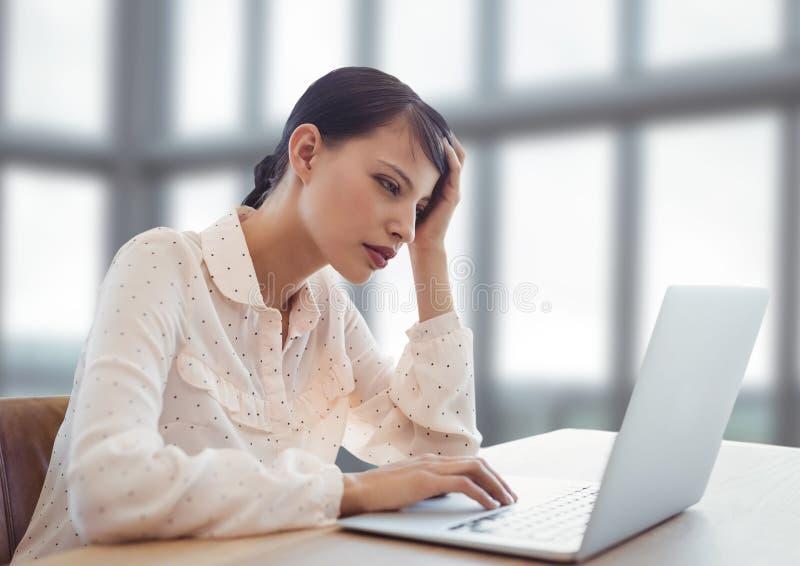 Affärskvinna som arbetar på bärbara datorn vid ljusa nya fönster royaltyfria foton