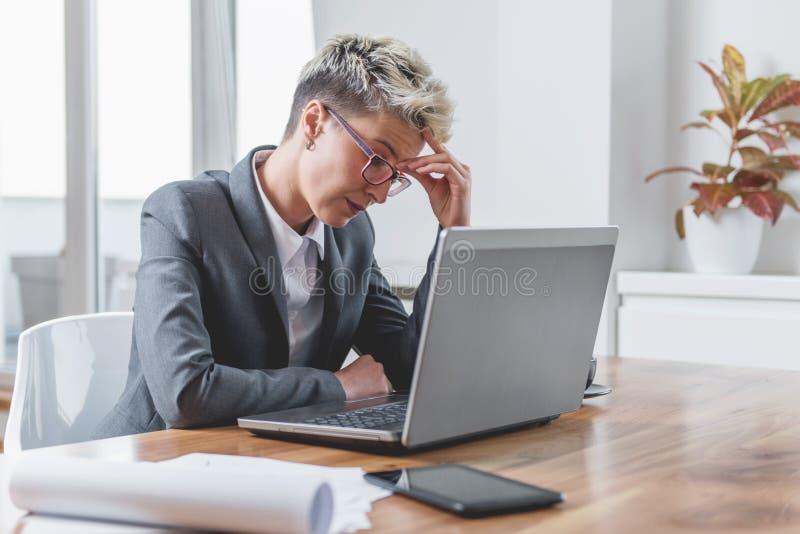 Affärskvinna som arbetar på en bärbar dator som överanstränger, under tryck royaltyfria foton