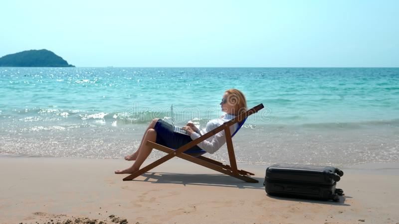 Affärskvinna som arbetar på en bärbar dator, medan sitta i en dagdrivare vid havet på en vit sandig strand frilans- eller workaho royaltyfria bilder