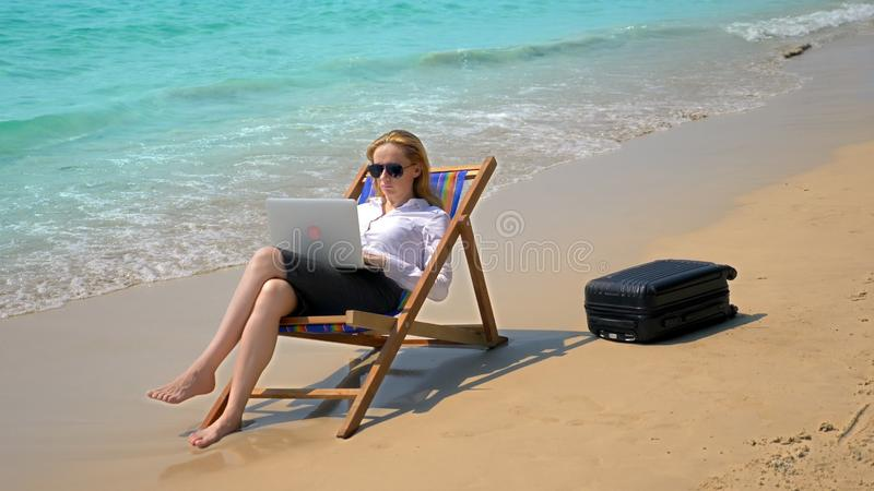 Affärskvinna som arbetar på en bärbar dator, medan sitta i en dagdrivare vid havet på en vit sandig strand frilans- eller workaho royaltyfria foton