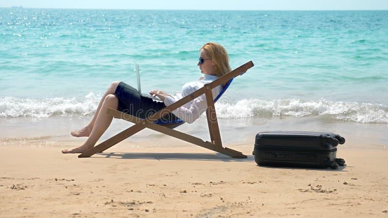 Affärskvinna som arbetar på en bärbar dator, medan sitta i en dagdrivare vid havet på en vit sandig strand frilans- eller workaho royaltyfri fotografi