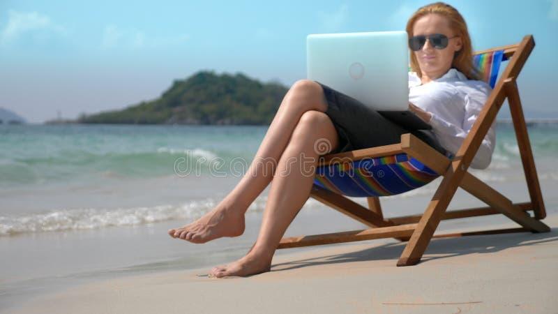 Affärskvinna som arbetar på en bärbar dator, medan sitta i en dagdrivare vid havet på en vit sandig strand frilans- eller workaho arkivbild