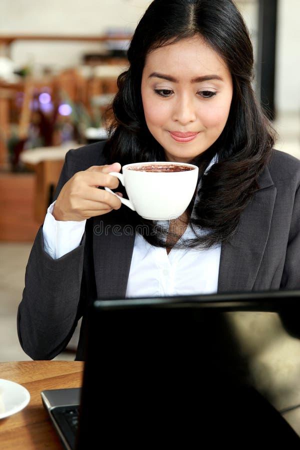 Affärskvinna som arbetar på hennes bärbar dator, medan ta ett kaffeavbrott fotografering för bildbyråer