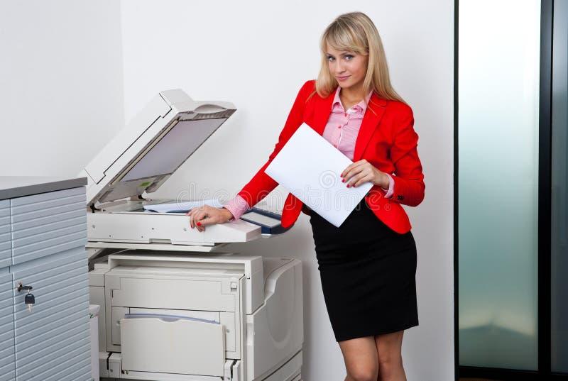 Affärskvinna som arbetar på kontorsskrivaren royaltyfri fotografi