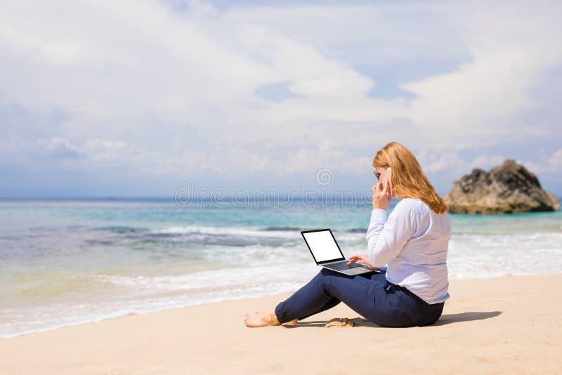 Affärskvinna som arbetar på stranden royaltyfria bilder
