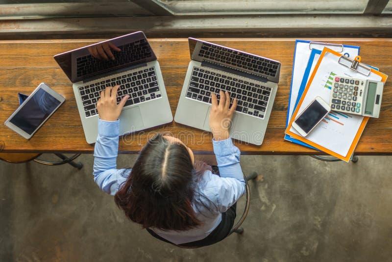 Affärskvinna som arbetar på två bärbara datorer royaltyfri fotografi