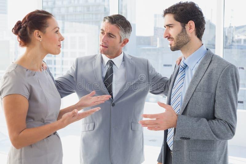 Affärskvinna som argumenterar med medarbetaren arkivbild