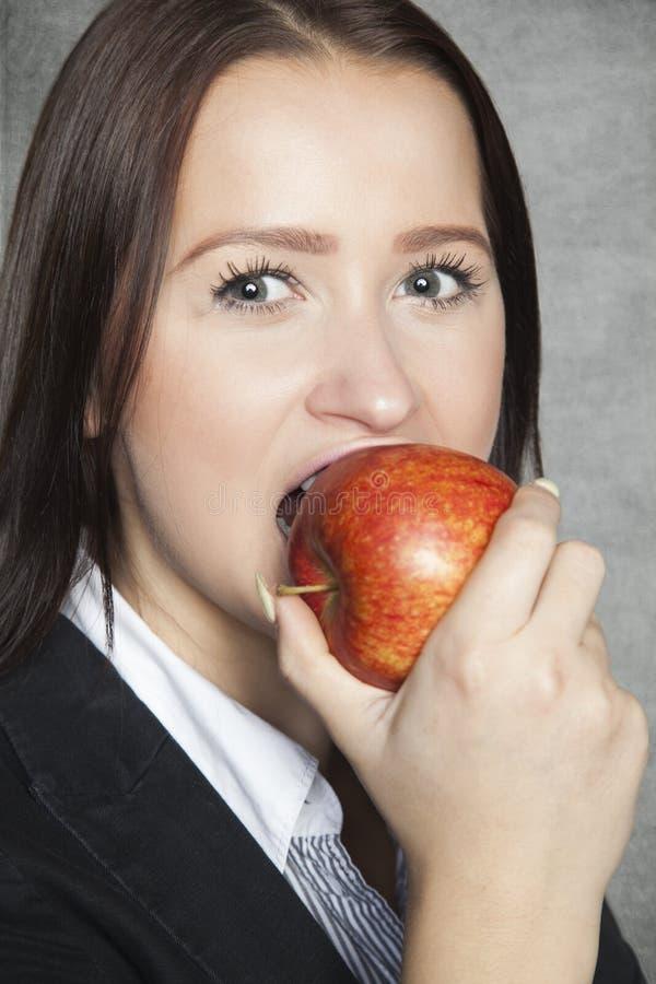 Affärskvinna som biter ett äpple arkivfoton