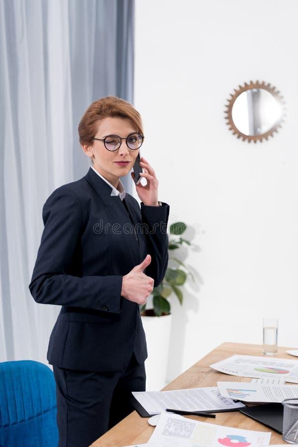 affärskvinna som blinkar på kameran och visar upp tummen, medan tala på smartphonen på arbetsplatsen royaltyfria foton