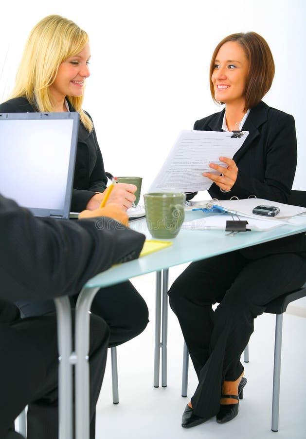 affärskvinna som diskuterar skrivbordsarbete två arkivbild