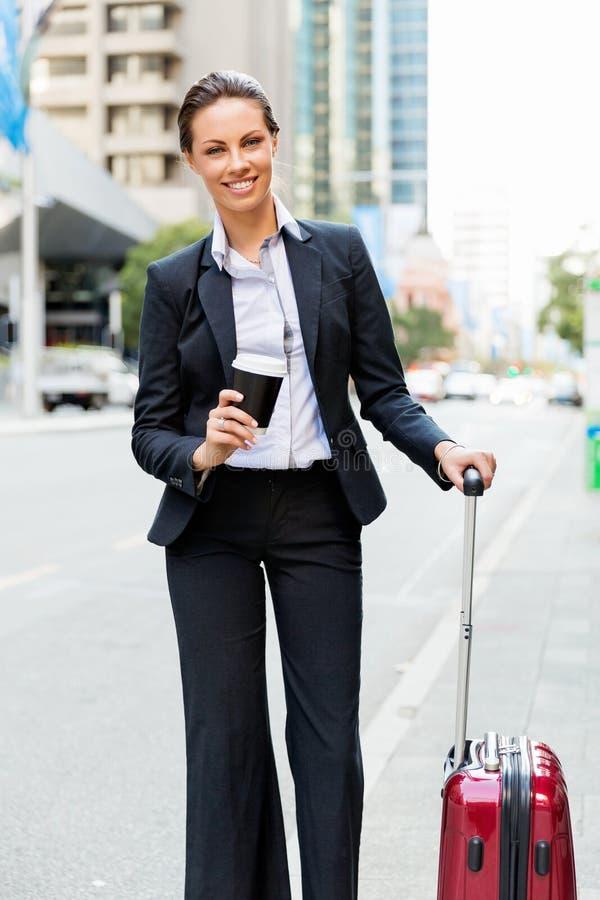 Affärskvinna som drar resväskan som går i stad royaltyfria foton