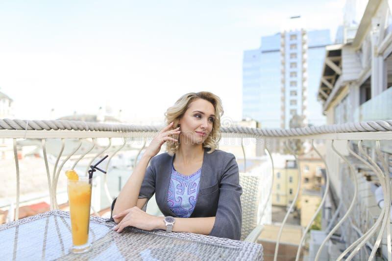 Affärskvinna som dricker fruktsaft på kafét på balkong med cityscapebakgrund arkivbild