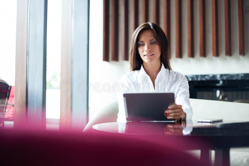 Affärskvinna som dricker kaffe eller te och använder minnestavladatoren i en coffee shop fotografering för bildbyråer